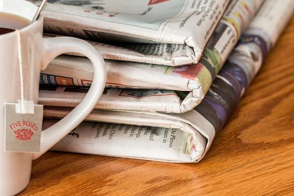 Foto van een houten tafel met drie kranten op en een theekop